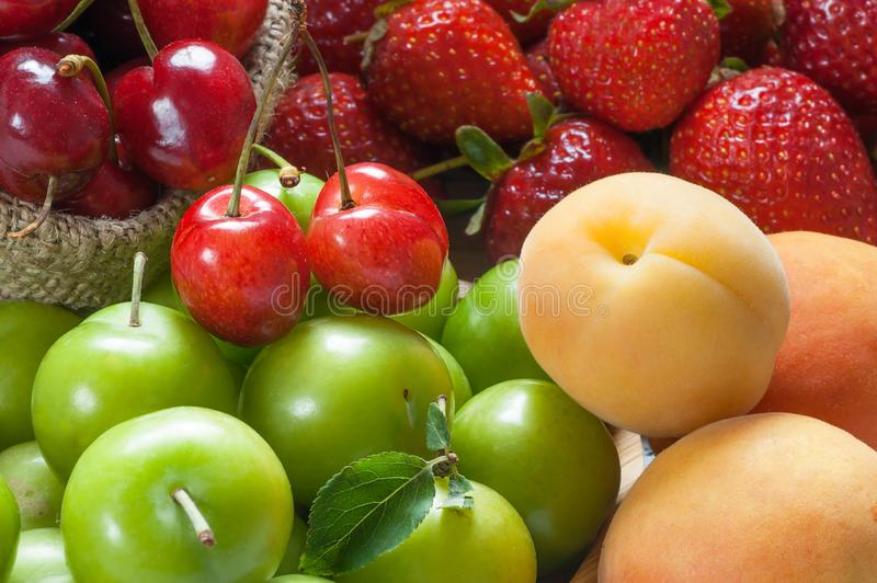 Close up summer fruits background, green plum, red cherry, strawberry, apricot stock photos