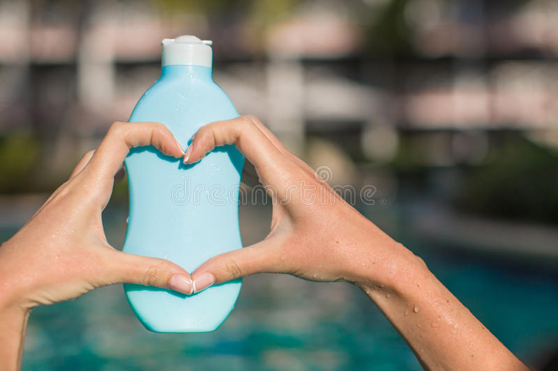 Close up of sunblock in female hands making heart stock photography