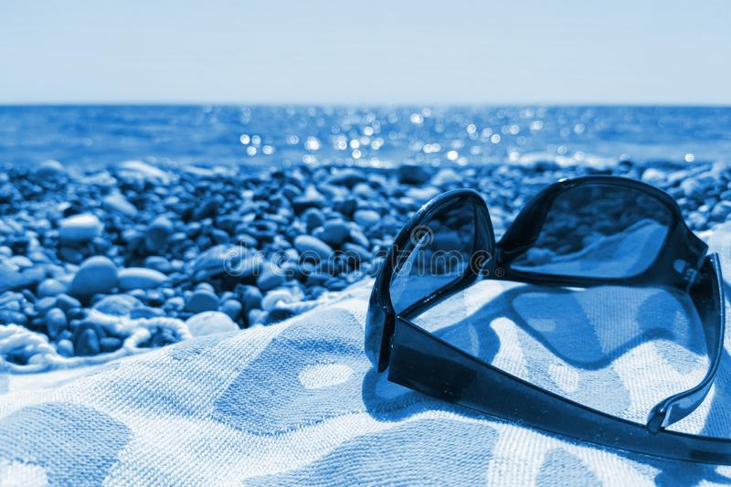 Close-up sunglasses on beach towel on pebbly sea beach. Trendy toning in color 2020 Classic Blue. Vacation concept. In trendy color. Selective focus, copy space royalty free stock images