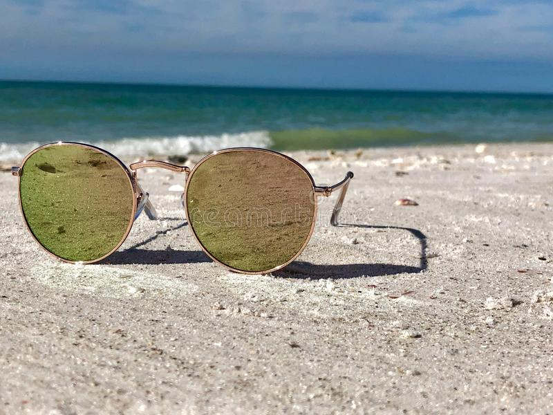 Close up of Sunglasses on a beach vacation. In Florida lying in the sand royalty free stock photos