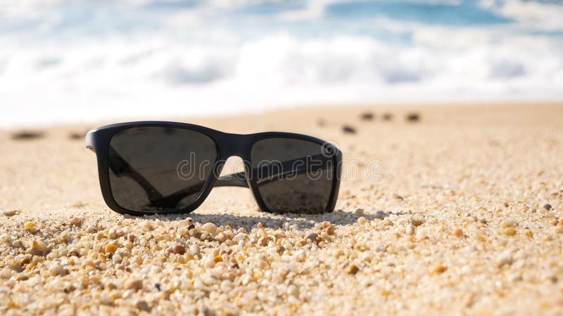 Close up of sunglasses on a sandy beach in summer. Shallow focus. Close up of sunglasses on a sandy beach in summer. Shallow focus with waves in background stock images