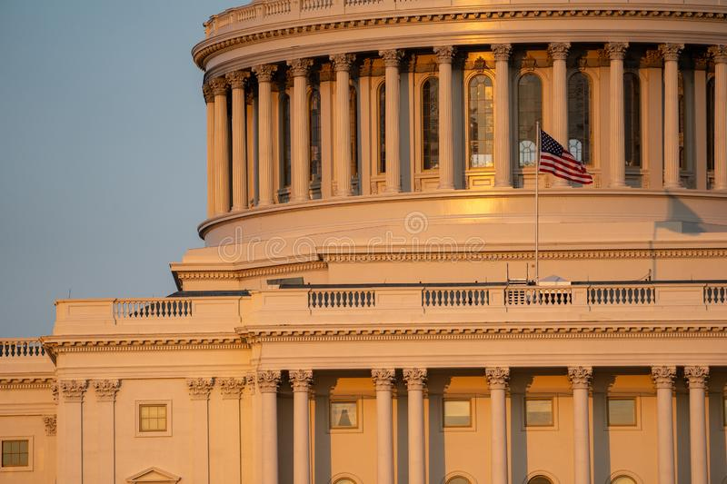 Close up sunset golden hour view of the US Capitol Building dome and columns, with the American Flag.  stock photography