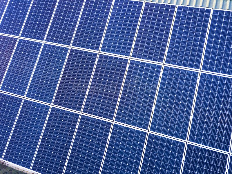 Close-up surface of blue shiny solar photo voltaic panels system on building roof. Renewable ecological green energy production. Concept stock photography