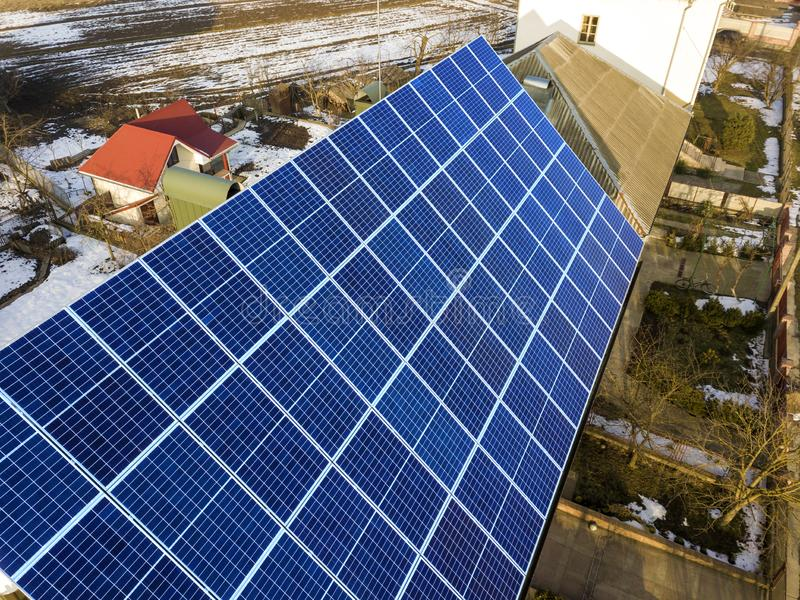 Close-up surface of lit by sun blue shiny solar photo voltaic panels system on building roof. Renewable ecological green energy. Production concept stock photo