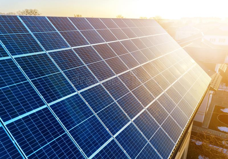Close-up surface of lit by sun blue shiny solar photo voltaic panels. System producing renewable clean energy. Renewable. Ecological green energy production royalty free stock images