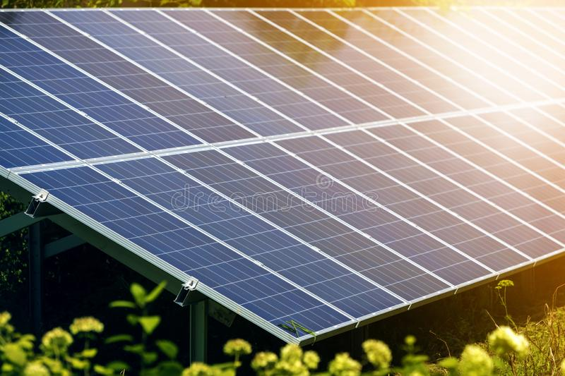 Close-up surface of lit by sun modern saving efficient stand -alone blue shiny solar photo voltaic panels system producing. Renewable clean energy on green stock photos