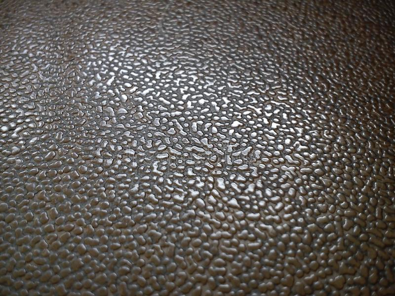 Close-up of the surface of a plastic seat. Pimples of different sizes and backgrounds reflect daylight. Drops, water, molten, mass, sweat, dew, reflection royalty free stock images