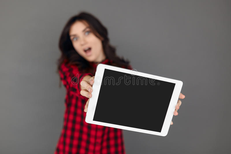 Close-up of surprised girl holding a blank screen tablet. royalty free stock photo