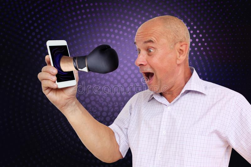 Close-up of a surprised, scared man holding a phone in his hand, from which a boxer strikes in a black boxing glove on a dark stock photography