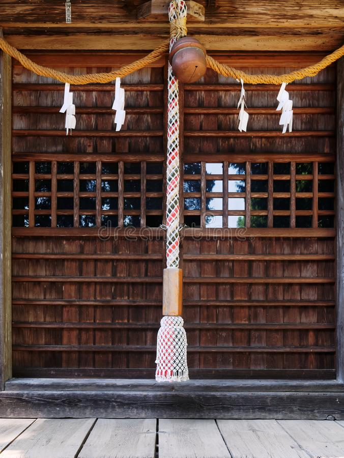 Close-up of Suzu Japanese Shinto bell and the rope hanging under the eaves royalty free stock image