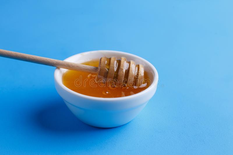 Close up of sweet and aromatic honey with wooden honey dipper on. Blue background, view from above royalty free stock photography