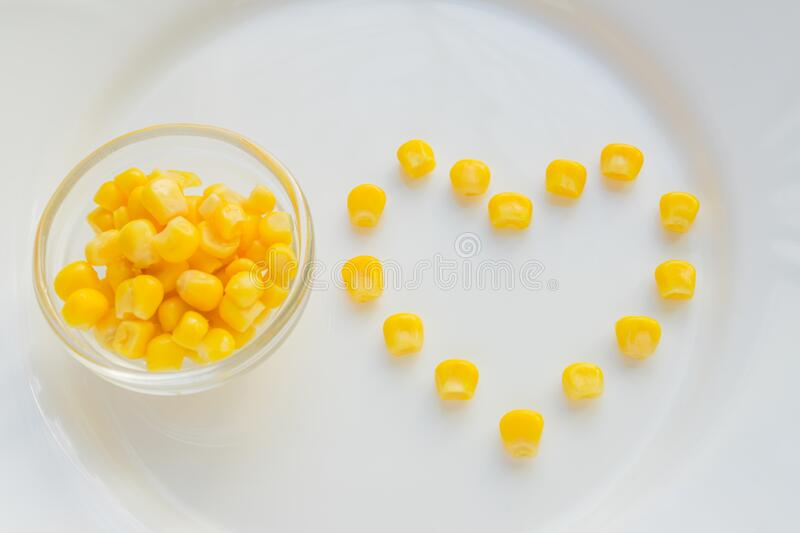 Close up of sweet corn in shape of heart  on white plate. Bowl with yellowe seeds. Close up of sweet corn in shape of heart on white plate. Bowl with yellowe stock images