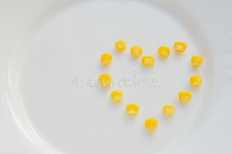 Close up of sweet corn in shape of heart  on white plate. Copy space for your text. Close up of sweet corn in shape of heart on white plate. Copy space for your royalty free stock images