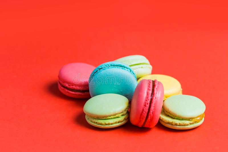 Close-up of sweet green, yellow, coral, blue macaroons on red background royalty free stock photos