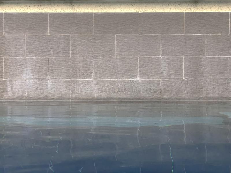 Close up of swimming pool with brick wall royalty free stock photography