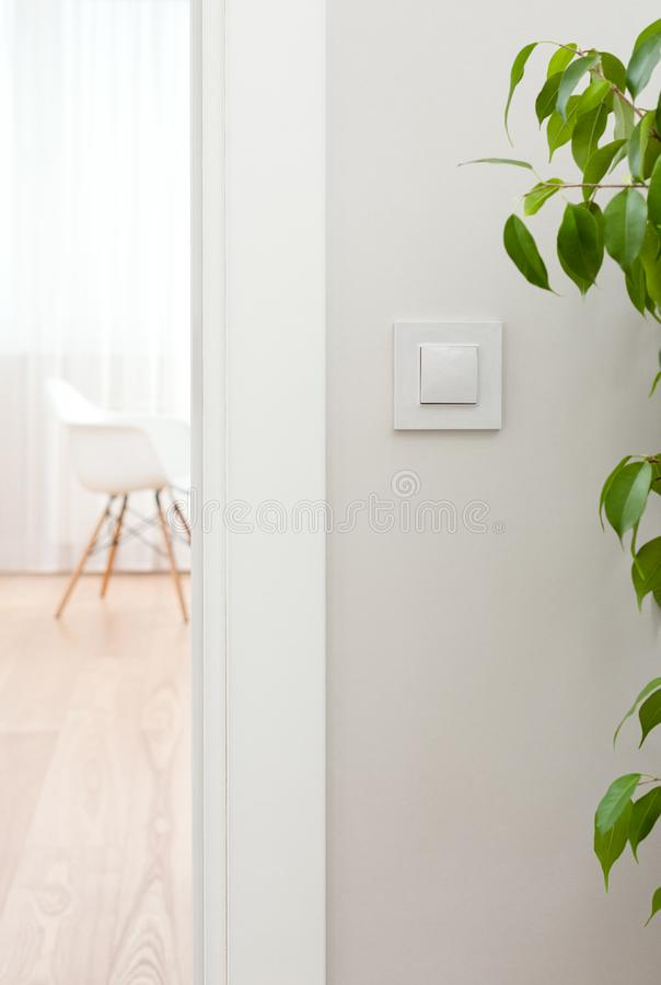 Close-up of switch on the wall. White, modern interior. Open the door to the room royalty free stock photo