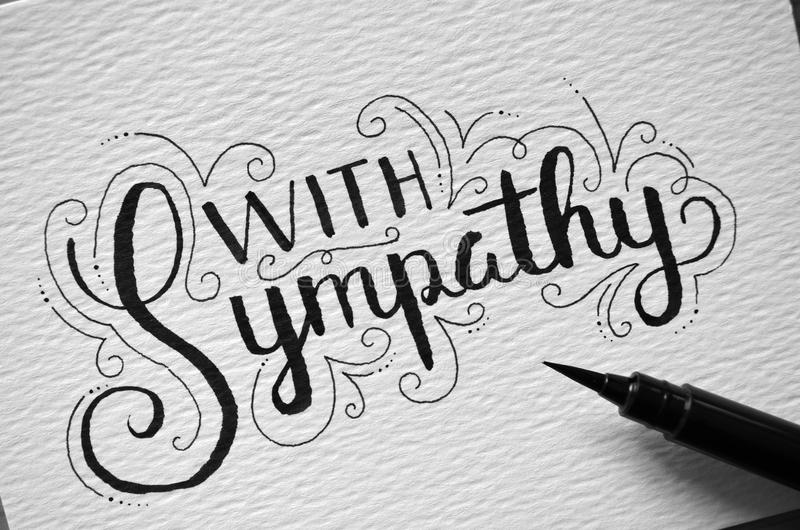 Close-up of `WITH SYMPATHY` hand-lettered on card. Close-up of `WITH SYMPATHY` hand-lettered in modern calligraphy style on card with brush calligraphy pen royalty free stock photos