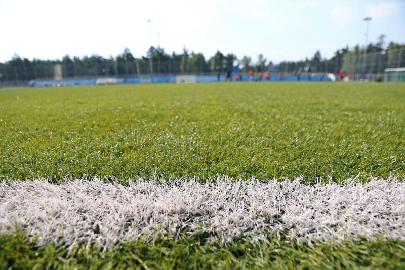 Close-up synthetic grass for football soccer sport field. Pattern of green artificial turf. Blurred soccer players on the background royalty free stock photos