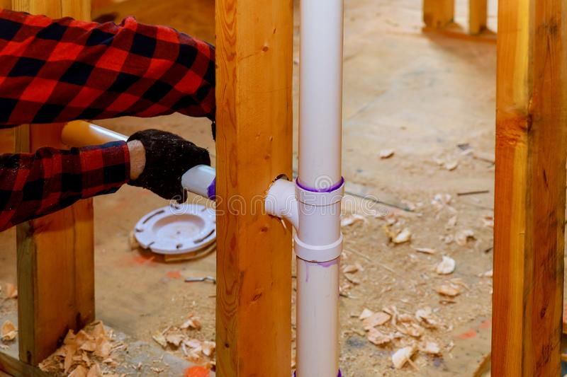 Close up on t joint and pipes for a home sewage system, in wood wall, drain and vent plumbing system stock image