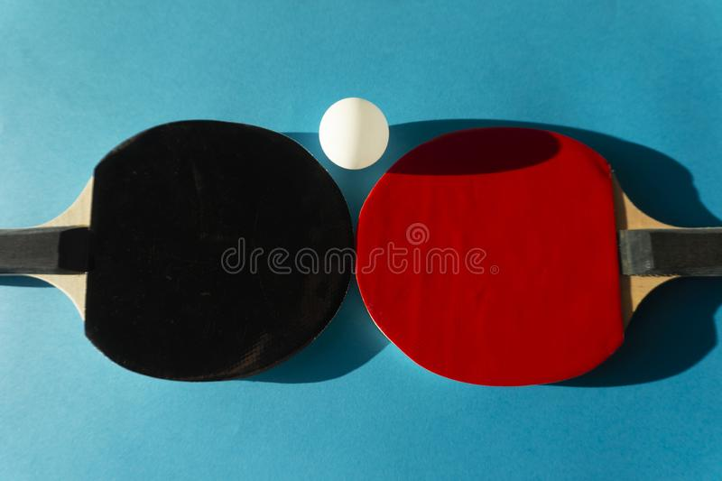 Table tennis bats and ball on blue copy space royalty free stock photography