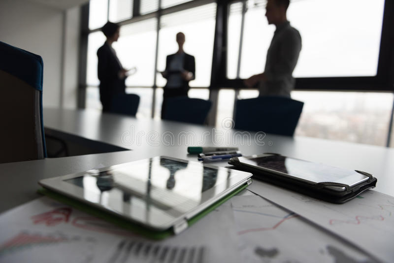 Close up of tablet, business people on meeting in background royalty free stock images