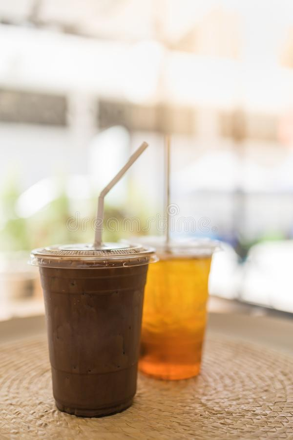 Close up of take away plastic cup of iced chocolate and iced tea on round table with copy space.  royalty free stock photos