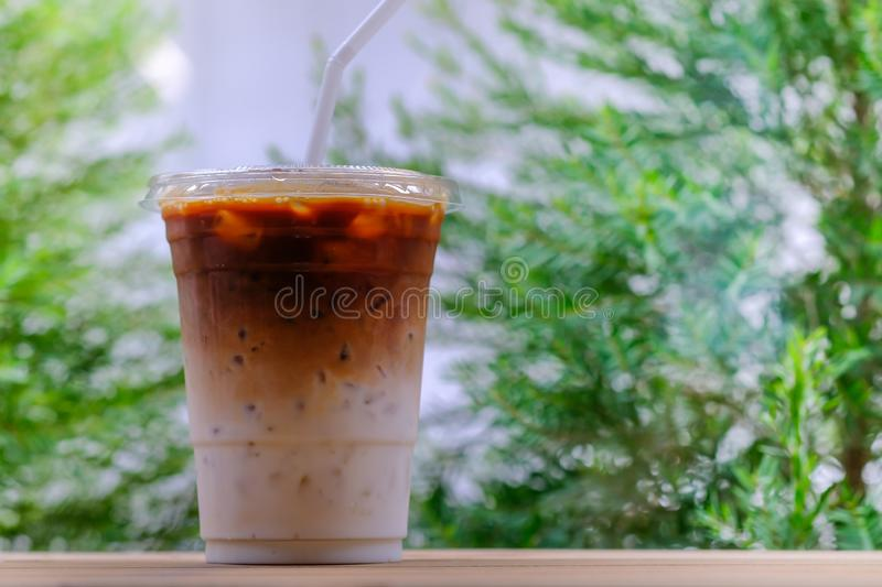 Close up of take away plastic cup of iced coffee latte on wooden table with green nature as background stock photo