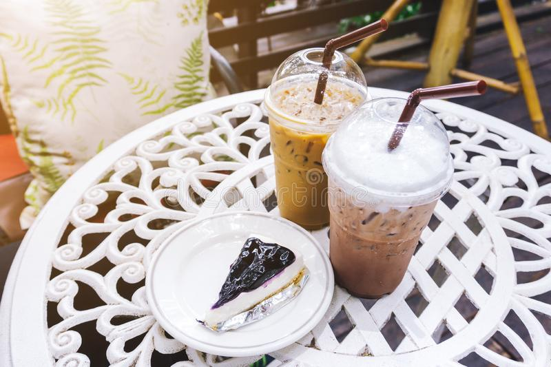 Close up takeaway plastic cup of delicious iced chocolate, iced coffee and blueberry pie on the table. Healthy refreshing summer d stock images