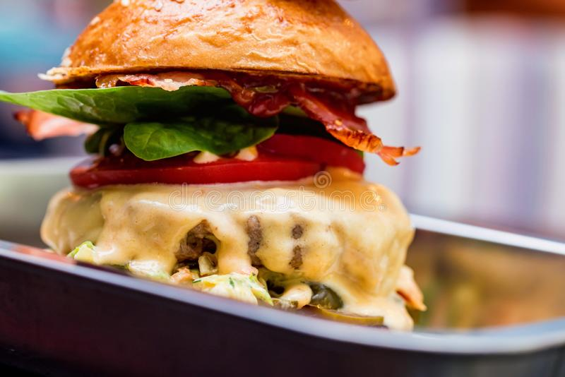 Close up tall tasty burger with cheese served on tray royalty free stock image