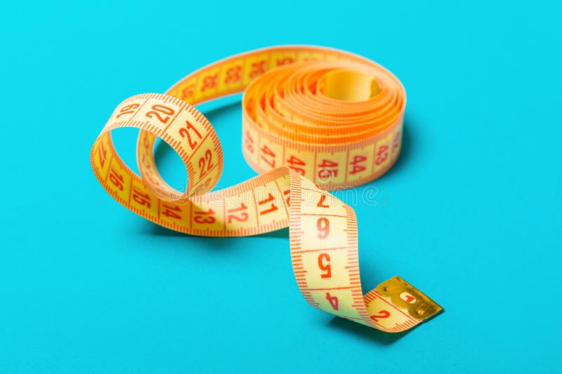 Close up of tangled measuring tape on blue background. Fitness and healthy diet concep with perspective view stock photography