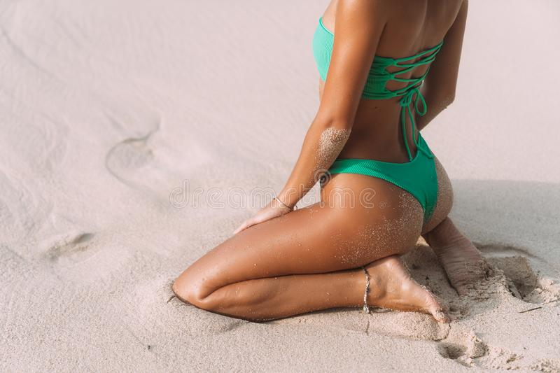 Close-up tanned buttocks of slender sporty girl on beach with white sand. royalty free stock images