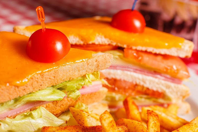 Close up Tasty grilled sandwich in the restaurant. Club sandwich with ham, tomato, cheese and lettuce. Served with royalty free stock image