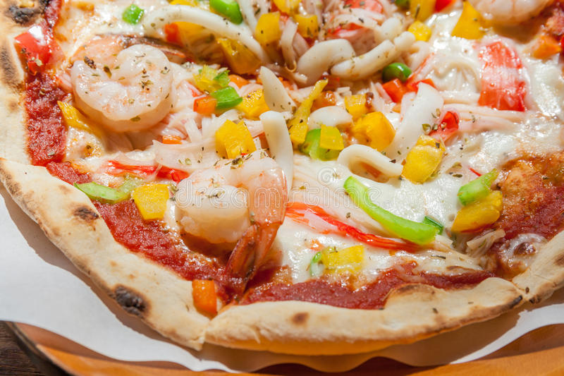 Close up of tasty homemade seafood topped pizza. Close up of tasty and crispy homemade seafood topped pizza, fusion food style royalty free stock photo