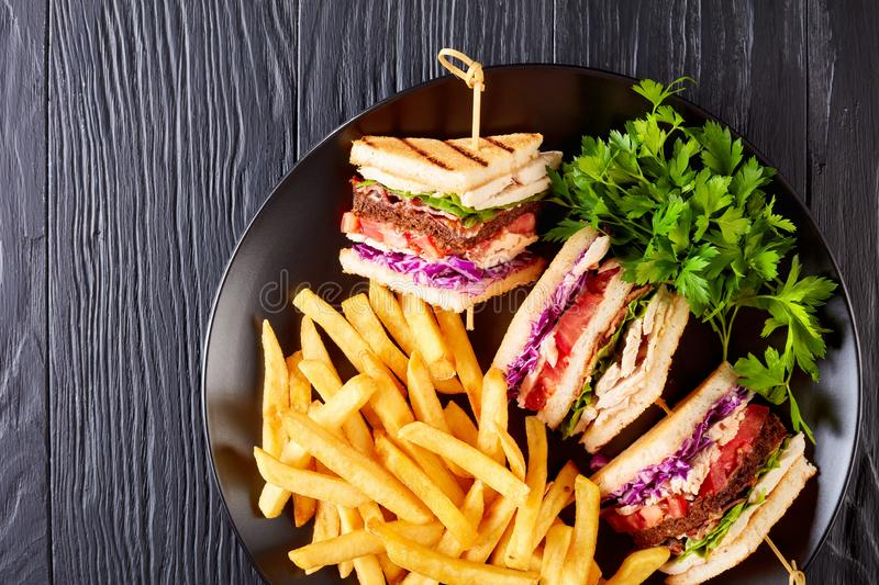 Tasty layered club sandwiches with french fries royalty free stock image