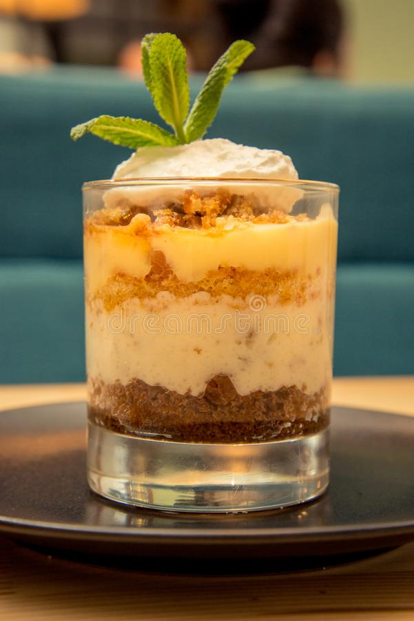 Close-up of tasty tiramisu on glass with mint on bistro table royalty free stock photo