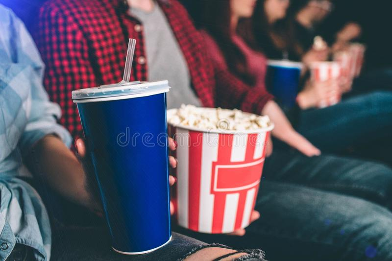 Close up of tasty but unhealthy food. There are basket of popcorn and a blue cup of coke on picture. Man and woman are stock photos