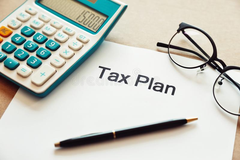 Close up tax planning word on paper with calculator, pen and eye glasses place on the wooden table stock images