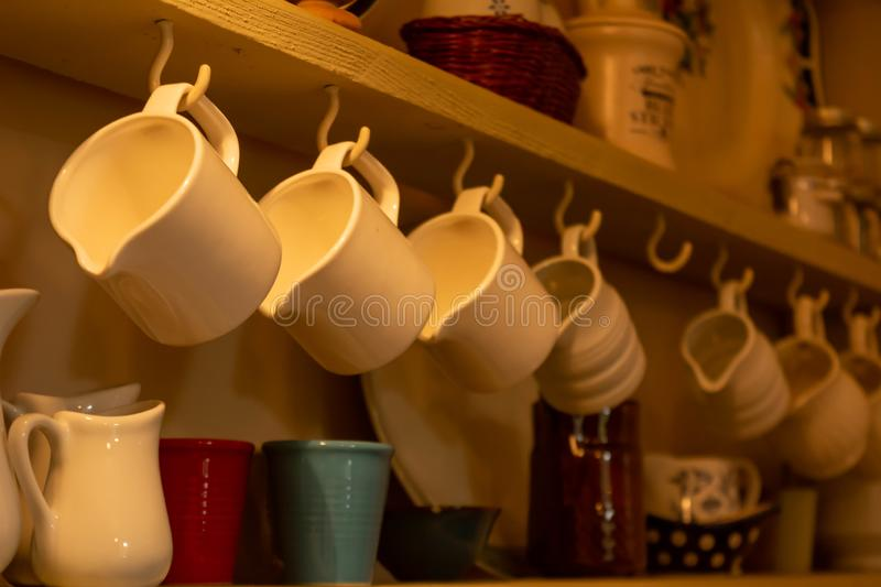 Close Up of Tea Cups Hanged on the Cupboard in English Cottage in Countryside. On Blurred Background, autumn, breakfast, calm, coffee, cold, drink, home, hot stock photo