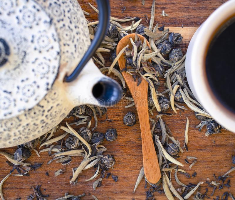 A close up of teapot, cup and tea leaves stock photo