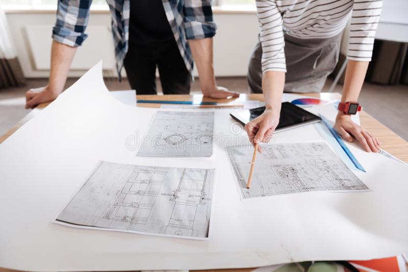 Close up of technical drawings lying on the table. Engineering developments. Close up of several technical drawings lying on the table with nice hard working stock image