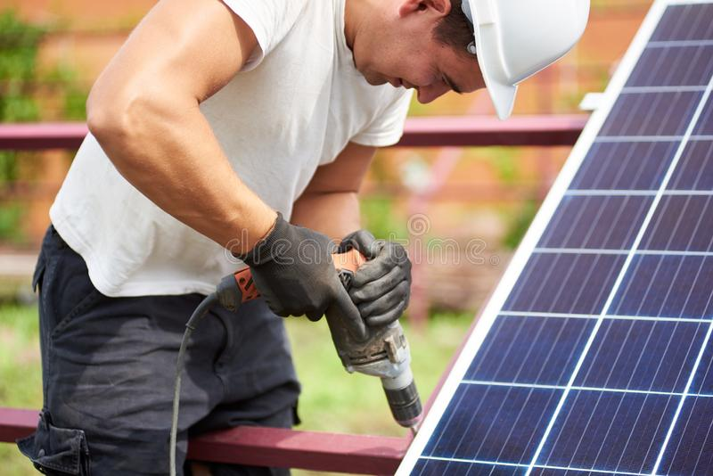 Installation of stand-alone exterior photo voltaic panels system. Renewable green energy generation. Close-up of technician in helmet connecting solar photo royalty free stock image