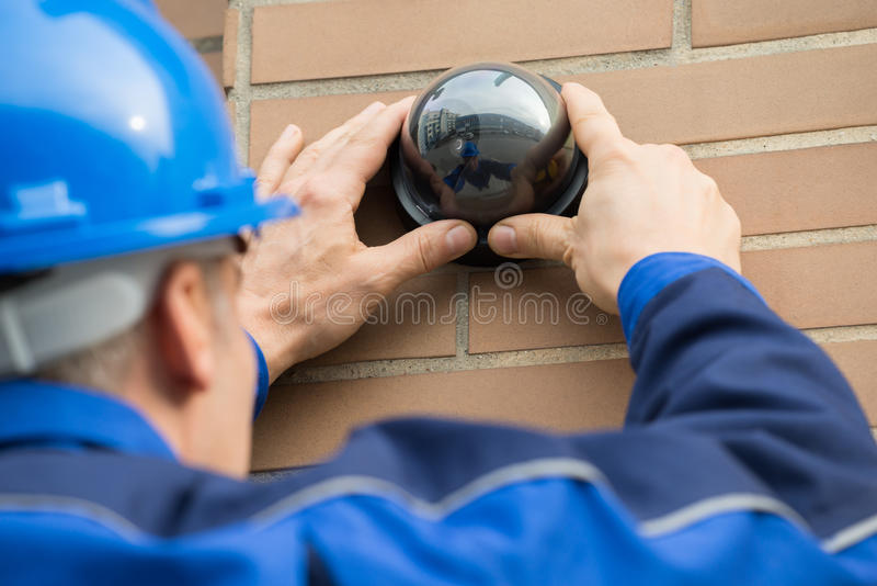 Close-up Of Technician Installing Camera In Building stock image