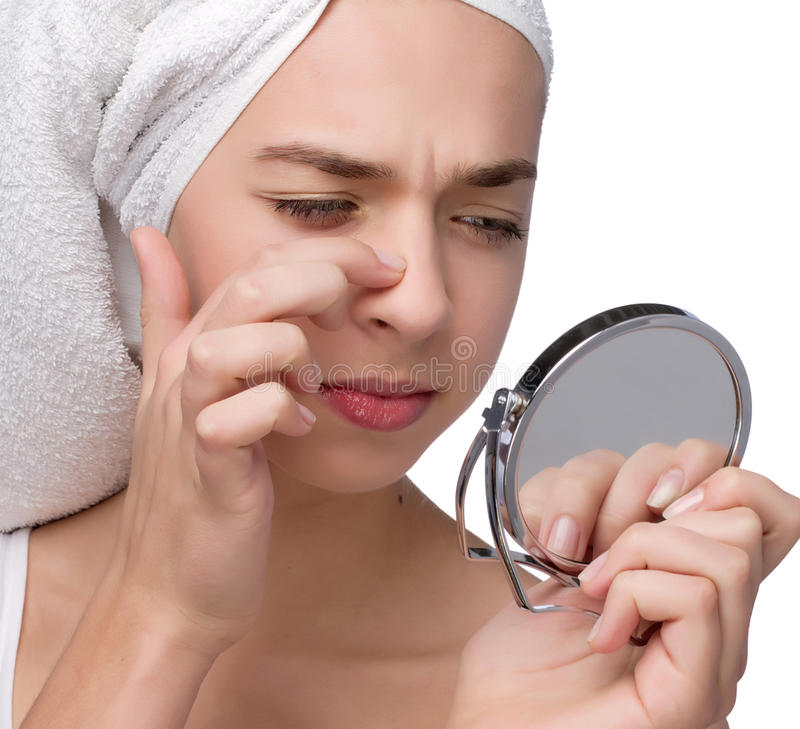 Close-up of teenager finding an acne on her nose royalty free stock image
