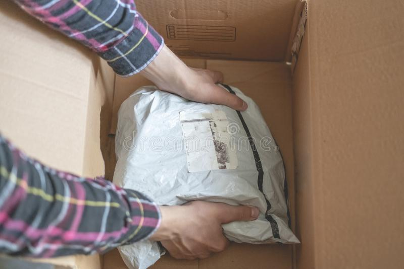 Close up teenager opens received the box package from the online store with new clothes f royalty free stock image