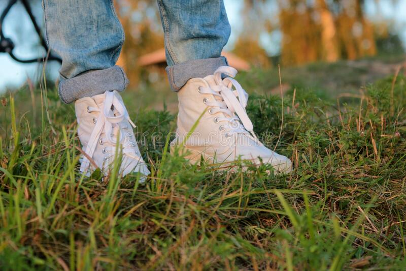 Close up of teenager`s feet in modern and trendy white sneakers and rolled up jeans. Sunny summer day, green grass background. Natural lighting stock photo