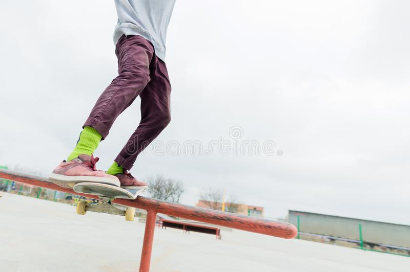 A close-up of a teenager`s leg of a skateboarder glides on a skateboard along the railing in the skatepark. The concept royalty free stock photos