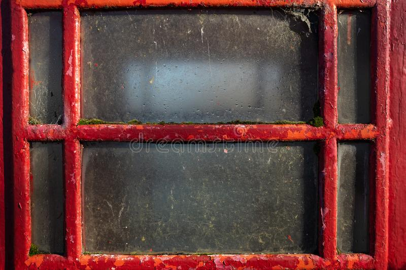 Close up of a telephone box window. Close up of a an old traditional red telephone box window royalty free stock image