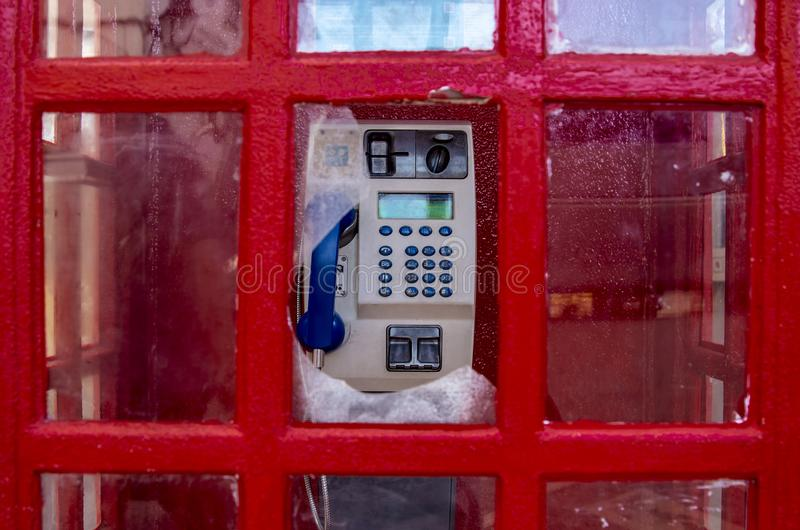 Broken window in a red telephone booth. Close-up of a telephone set through a broken window in a telephone booth. Classic English red telephone box stock photo