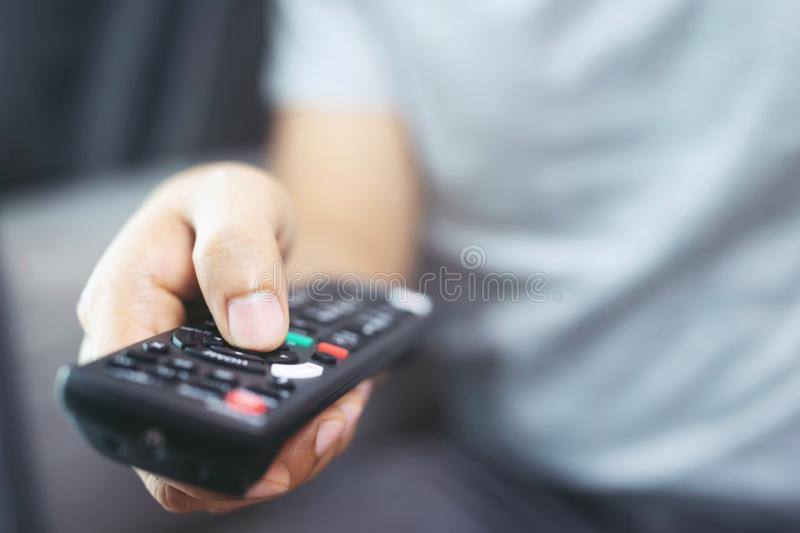 Close up Television remote control in casual man hands pointing to tv set and turning it on or off. royalty free stock photography