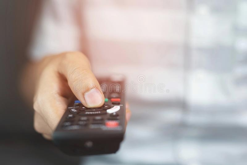 Close up Television remote control in casual man hands pointing to tv set and turning it on or off. select channel watching tv stock photos